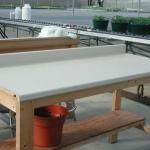 Clean greenhouse work table with non-porous surface