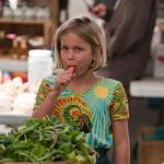 Amherst Farmers' Market child enjoys fresh carrot