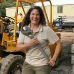 Christine Hatch wields large wrench as she assembles fiber-optic plow
