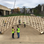 Wood dome shell raising with Design Building in background