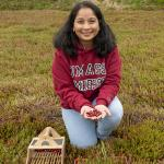 Sai Sree in bog holding cranberries