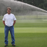 Scott Ebdon with high-arc sprayer watering turf