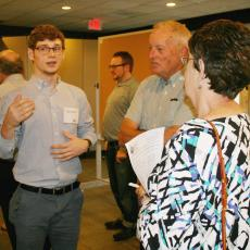 Dungan Becker explains his work during Summer Scholar poster session to Massachusetts Grange members, Scott Davis and Kathy Peterson, Chair, Executive Committee