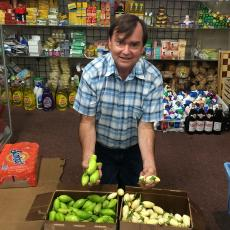 Frank Mangan of the Stockbridge School of Agriculture at Monrovia African Market in Worcester holding garden egg (white) and jiló (green) grown at the UMass Research Farm in Deerfield MA