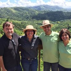 On a visit to Puerto Rico to talk about collaborations to provide culturally-appropriate fresh produce to Latino markets in Massachusetts, Frank Mangan (left) is shown with Puerto Rican Secretary of Agriculture Dr. Myrna Comas-Pagán, and the owners of the coffee farm in the background.