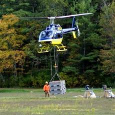 Helicopter lifting cranberries out of bog to waiting trucks