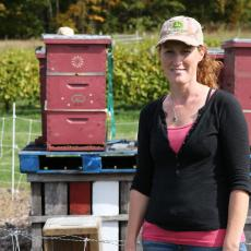 Kristen Hanley, Orchard Administrator checks bee hives