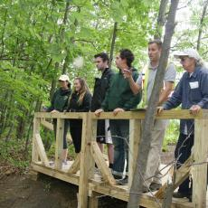 UMass students,Tara McElhinney and Jack Mulcahy, review invasive speciees with residents at Abbey Brook, Springfield