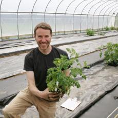 Jacob Barnett plants tomato seedlings he grew from seed, May 2019