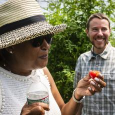 Council member Danah Tench samples a tomato supplied by grad student Jake Bartlett