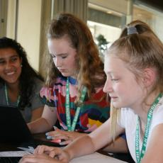 Three 4-H young women work on creating a phone app