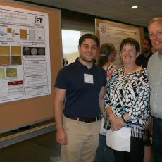 Adam Salhaney, senior, shares poster information with Kathy Peterson and Scott Davis, Mass Grange