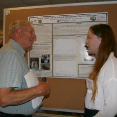 Scott Davis, Mass Grange, picks up some honey bee tips from student Bryanna Joyce at poster session