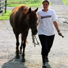 Student walking horse at the Hadley Farm