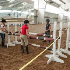 Students setting up horse jump at Hadley Farm horse barn