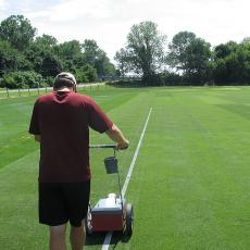 A graduate student paints lines on the grass tennis court research plots at the Joseph Troll Turf Research Center.