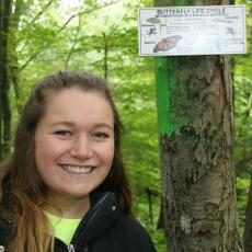 Tara McElhinney with interpretive signage she posted