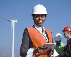 Woman Standing in Front of Wind Turbine with Men in Background