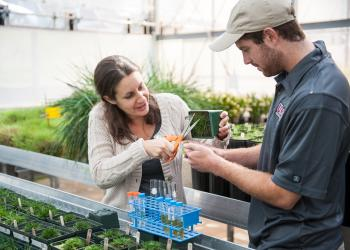 Michelle DaCosta trains student in greenhouse