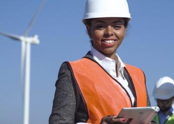 woman in hardhat in front of wind turbine