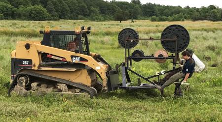 Hatch drives fiber optic plow on skid steer through bog laying cables within the bog