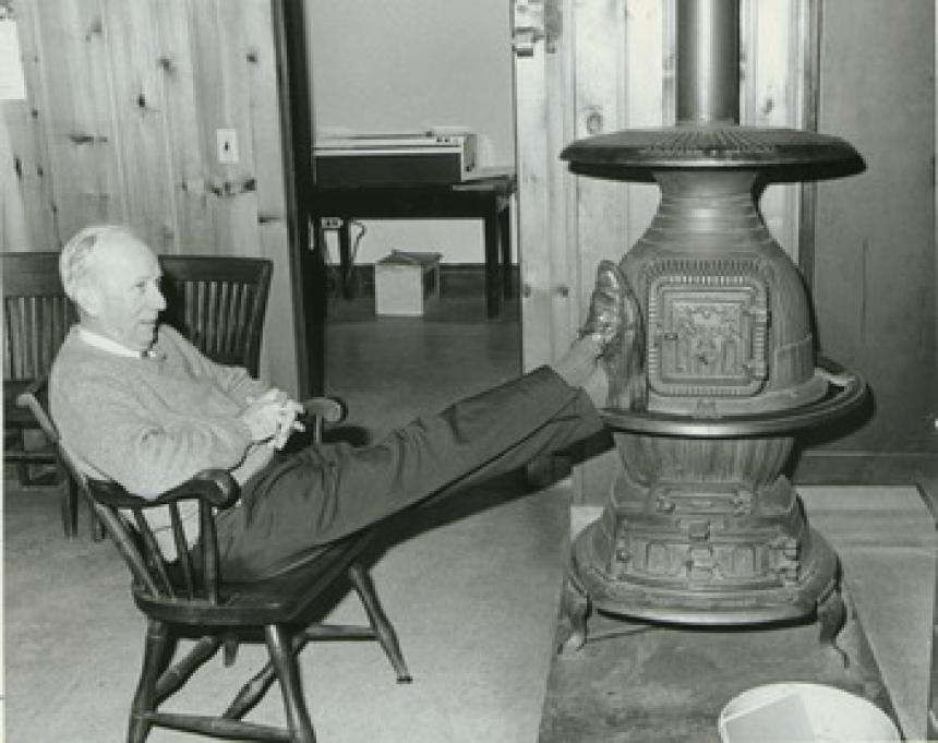 Dr. Chester Ellsworth Cross, with feet on woodstove
