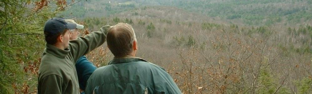 Three foresters discuss land conservation from atop a mountain