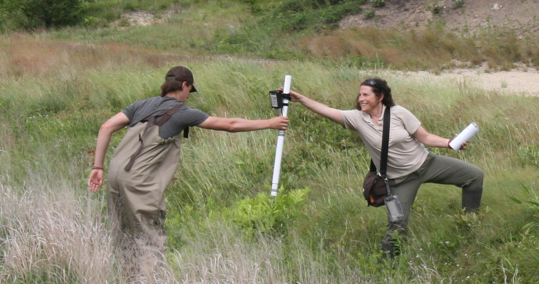 Luke McInnis hands soil moisture probe to Christine Hatch