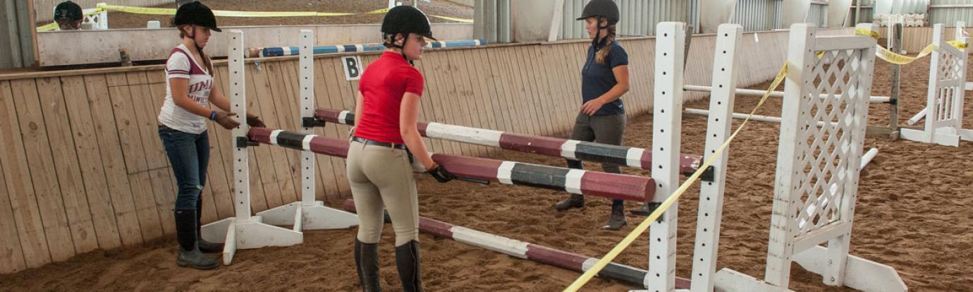 Students setting up horse jump at Hadley Farm horse barn