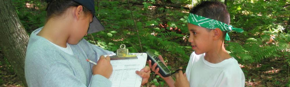 two kids collecting forestry data