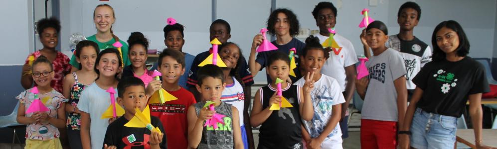 a group of kids holding paper rockets